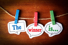 The winner is. Concept paper speech bubbles with line on the wooden background Royalty Free Stock Photo