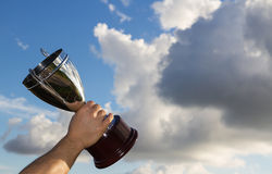 The Winner with Cup. Winner with cup in hand to the sky Stock Photo