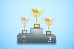 Winner cups on blue background. Sports pedestal with golden, silver and bronze winner cups on blue background. 3D Rendering Stock Photo
