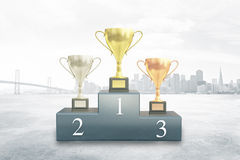 Winner cups on city background. Sports pedestal with golden, silver and bronze winner cups on city background. 3D Rendering Stock Photos