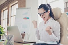 Winner! A dream of the young cute entrepreneur came true. She is. Very excited, wearing smart outfit, celebrating at the work place royalty free stock photos