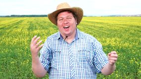 Winner! A dream of the young fat farmer came true. He is very excited, wearing hat, celebrating. Stands in the field on a sunny day with hands raised up stock video footage