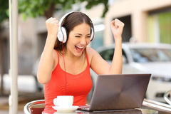Winner girl euphoric watching a laptop. In a coffee shop wearing a red shirt royalty free stock image