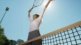 Winner jumping at the net and laughing happily celebrating her triumph after winning tennis match stock footage