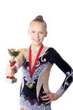 Winner gymnast girl holding award. Portrait of beautiful happy smiling fit gymnast or skater young woman in sportswear dress posing with golden cup and first Stock Photos