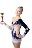 Winner gymnast girl holding first place cup. Portrait of beautiful happy smiling cool fit gymnast or skater young woman in sportswear dress posing with golden Stock Image
