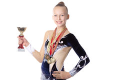 Winner gymnast girl. Portrait of beautiful happy smiling cool fit gymnast or skater young woman in sportswear dress posing with golden cup and first place medals Stock Images