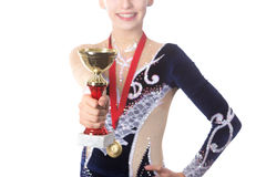 Winner gymnast girl showing award. Portrait of beautiful happy smiling fit gymnast or skater young woman in sportswear posing with golden cup and first place Royalty Free Stock Images
