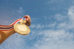 Winner hand raised and holding gold medal against blue sky. succ. Ess award concept Stock Image
