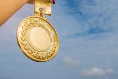 Winner hand raised and holding gold medal against blue sky. succ. Ess award concept Royalty Free Stock Photography