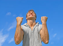 The winner, happy energetic young man. The winner. Happy energetic young man on blue sky background royalty free stock photos
