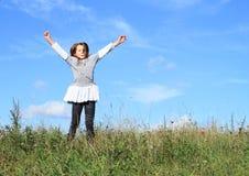 Winner - happy girl in grass. Little kid - happy winner girl in grass of green meadow with blue sky behind Stock Photos