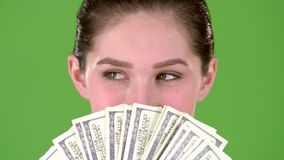 Winner holds a lot of money in her hands. Green screen. Close up. Slow motion. Winner holds a lot of money, she is very rich and wealthy after the lottery. Green stock footage