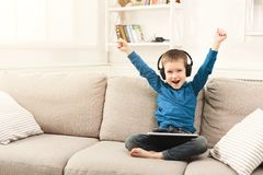 Little boy using digital tablet on sofa at home. Winner! Little boy in headphones won online game on tablet, having fun at home. Gadgets and technology, success Royalty Free Stock Photography