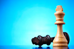 Winner and loser. Depicted by two chess pieces with the black king lying on its side dominated by the wooden king against a blue background with highlight and Stock Image