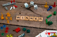 `Winner` made from Scrabble game letters. Risk, Battleship pieces, Monopoly, Settler of Catan and other game pieces royalty free stock images