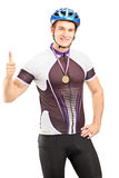 Winner male cyclist with a golden medal giving a thumb up. Isolated on white background Royalty Free Stock Photos