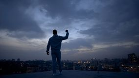 Winner man enjoying success on night cityscape background, personal leadership. Stock photo royalty free stock photo