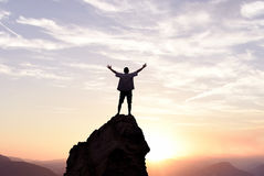 Winner man standing on the top of mountain. Man with arms raised in the sky winner success concept Stock Photo