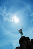 Winner man standing on the top of mountain vertical image Stock Photo