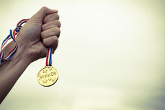 Winner Medal Champion Success Motivation Concept. Hand holding winner medal over sky as motivational success winning victory concept royalty free stock photography