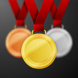 Winner medals. Set of winner medals with red ribbon isolated on dark background royalty free illustration