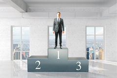 Winner on pedestal in interior. Businessman on first place pedestal in interior with brick wall and concrete floor. 3D Rendering Royalty Free Stock Images