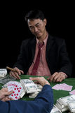 The winner player gather the bets and show the points over rival. The winner gambler is gather the piles of banknote on the green table and show winner with stock image