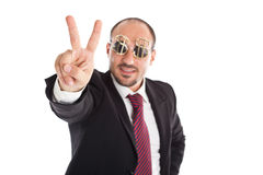Winner sign. Businessman with dollar-sign glasses standing and showing the win sign. Focus on the hand Royalty Free Stock Images