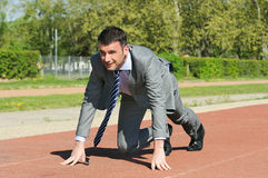 Winner start. Portrait of a businessman on the starting blocks stock photography