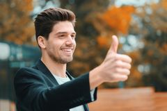 Winner. Success. Brunette young man in business clothing in office district smiles to camera and gives thumbs up. Happy stock image