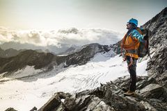 Climber with big smile on his face. Winner/Success concept. Climber enjoying a view from the mountain top after climbing the exposed rocky and snowy mountain Stock Photos