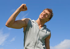 The winner. Successful and energetic young man. The winner. Energetic young man with his arm raised in joy Stock Photo