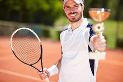 Winner in tennis holding beaker and racket. Male winner in tennis holding beaker and racket Royalty Free Stock Photography