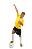 The winner took the first place. A happy boy with his leg on a soccer ball isolated on a white background. Full-length. A smiling schooler with a raised hand and Stock Photo