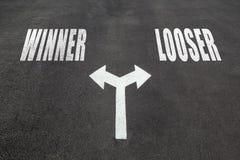 Winner vs looser choice concept. Two direction arrows on asphalt Stock Photos