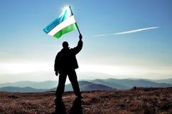 Winner waving Uzbekistan flag on top of the mountain peak. Successful silhouette man winner waving Uzbekistan flag on top of the mountain peak stock photo