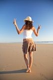 Winner woman with hat walking at beach Stock Photos