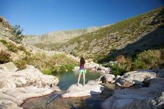 Winner woman on a rock watching river Stock Photo