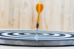 Winner Yellow dart arrow hit the center target of dartboard meta. Phor marketing competition concept, on wood background Royalty Free Stock Photography