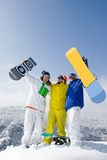 Winners. Portrait of three successful snowboarders raising their arms on mountain top Stock Photo