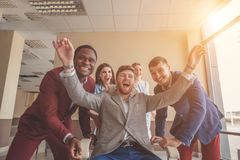 We are the winners. business people having fun while racing on office chairs. Who is the winner Four young cheerful business people in smart casual wear having Stock Photo
