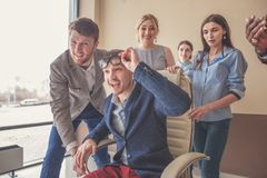We are the winners. business people having fun while racing on office chairs. Who is the winner Four young cheerful business people in smart casual wear having Royalty Free Stock Photo