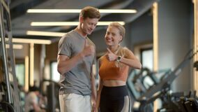 Winners couple showing like signs in sport club. Couple enjoying results at gym