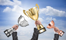 Winners. Holding champion golden, silver and bronze trophies royalty free stock photo