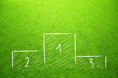 Winners podium sketch on soccer grass. Winners podium sketch on sunny artificial green soccer grass background stock photography
