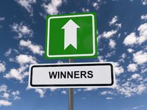 Winners. Text 'winners' in black uppercase letters on a white rectangular highway style sign with bold white arrow above and blue sky and cloud background royalty free stock photos