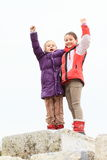 Winners on top. Little kids - happy young girls in winter clothes standing on the top of mound of rocks as friends and winners stock image