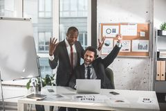 Happy businessmen are expressing gladness in office. Winners. Two optimistic managers in suit are celebrating successful completion of their project. They are royalty free stock images