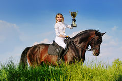 Winners - young girl and bay horse. With cup stock images